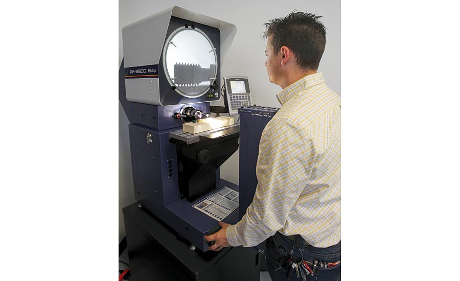 A metrology student inspects thread details of a go-no gage on the optical comparator.