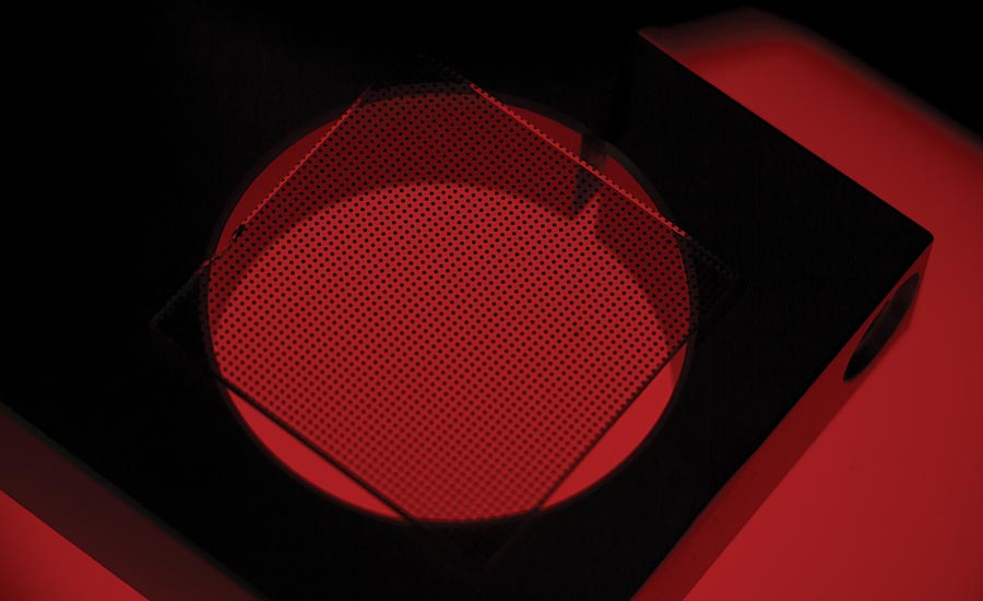 A calibration grid seated on a piece of tooling above a red backlight.