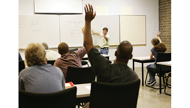 man raising arm in class student