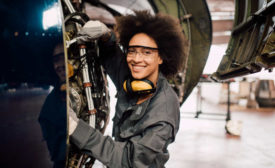 smiling woman working on an airplane engine